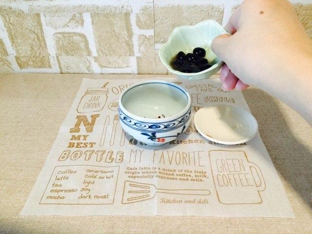 黒豆コーヒーカップに黒豆と煮汁を入れる